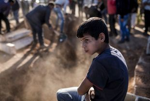 A young boy looks on as mourners cover with soil the grave of a Kurdish Protection Unit (YPG) fighter who died during fighting in the besieged Syrian border town of Kobane, in the town of Suruc, Sanliurfa province, Turkey on November 6, 2014.