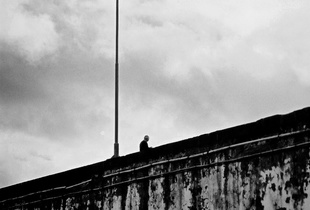 Man stares at the sea from the top of the pier, Ponta Delgada, Azores, Portugal, 2005