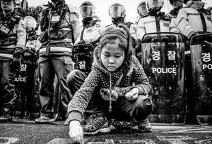 A young protestor draws with chalk on a street blocked by police, in front of the KEPCO office in Miryang. The city has seen many demonstrators from across the country since the dispute began two years ago. © Ben Weller