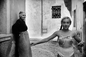 "A young girl wears a ""bikini"" in Dubrovnik small streets, under the disapproving look of her grandmother. Yugoslavia, 1953"