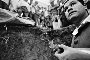 Anthropologist Danny Guzman shows a human jawbone to family members gathered at the graveside to aid in identification of a body. The work of the FAFG is physically and emotionally challenging, as well as dangerous -- they regularly receive death threats and harassment for the politically sensitive work of digging up Guatemala's past. © Victor Blue, 2004