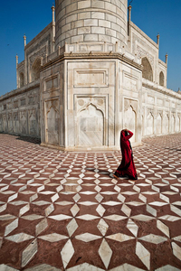 Agra, India: A woman passing the crown of palaces. The white marble mausoleum of Taj Mahal. © Matjaz Krivic