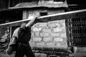 A man carrying materials for rebuilding houses destroyed by the 2015 earthquake. Barpak, Gorkha District.