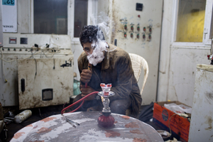 Jamal, 17, smokes flavored tobacco from a small hookah pipe inside the utility cabin. 19/02/15.
