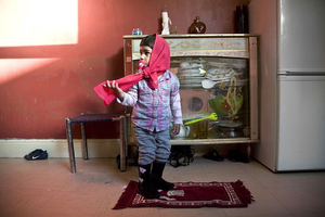 "First prayer mat A three-year-old in her kitchen with the ""baby"" prayer mat used previously by her older brother and sister. It was given to her British-born Muslim mother and Pakistani-born father on the occasion of their arranged marriage. © Liz Hingley"