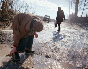 "A woman cleans mud off her shoe. From the series ""From the Mountains and to the Sea"" © Nadia Sablin"