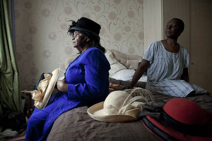 Mrs Adina Clarkes church hats  Jamaican-born Mrs Adina Clarke and her daughter review her hat collection before church. In keeping with Jamaican tradition, Adina reserves a part of her wardrobe for Sunday clothes and refrains from wearing them for any occasion other than church. Elaborate hats are a striking sight on Soho Road buses every Sunday. © Liz Hingley