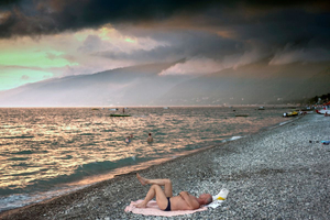 Gagra, Abkhazia. A man lies on a towel on the pebble beach at Gagra, the busiest seaside resort in Abkhazia. Dark clouds gather over the mountains in the distance. Gagra is a mere 20 kilometres from the Russian border.© Petrut Calinescu