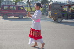 A Maibi priestess shaman of the Manipuri faith of the Umang Lai, dances in procession as the busy city of Imphal circles around her.