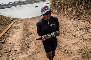 Team Leader Sok Chenda carries a 105mm round from the banks of the Tonle Sap River, the team where informed of the round whilst conducting reconnaissance in the area.