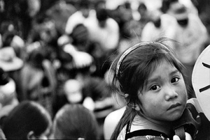 A young girl stares back from the edge of a grave. The legacy of the violence of the war years will continue to haunt her country for generations to come. The exhumations of the disappeared is only a first step in repairing the fractured society she has inherited. © Victor Blue, 2004