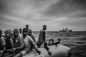 Migrants call out to be rescued from a rubber boat by the MOAS rescue team