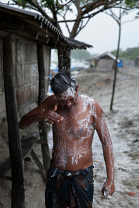 A man trying to shower in the rain but it has been stopped suddenly.