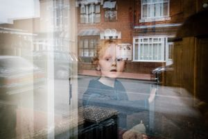 Jacob Robinson, 8, opens the door of his home on Robinson street. The family is the only British family living on their street. Smethwick, England, 2016.
