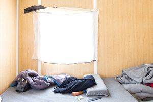 A sleeping infant barely protected from the searing sun in a prefab in Zaatari RC. © David Brunetti