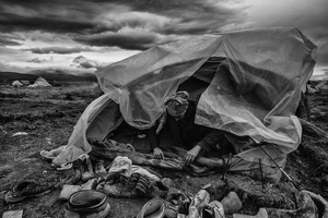 A woman tries to fix his tent, after heavy rains and strong winds have destroyed almost everything.