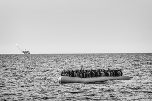 An overcrowded rubber dinghy sailing from Libya to Italy, Strait of Sicily,Mediterranean Sea, 26 August 2015.