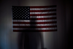 Manny Bojorquez casts a shadow on a flag in his apartment in Mesa, Arizona. He was a member of the 2/7 Marines, which fought in Afghanistan in 2008 and now has a suicide rate more than 10 times higher than the national average.