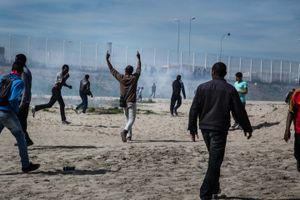 August 2016, Calais, France. Refugees try to cut the fences and slip trough towards the trains or boats going to the UK and play a cat and mouse game with the massive police presence . At the end of the summer of 2016 almost 10.000 refugees were living in the Jungle Camp in Calais, with tensions rising.