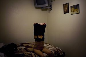 A prostitute undresses for a client in a short-term motel in Nogales, Sonora. © David Rochkind