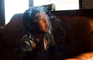 Dihan Muhamad, whose father smokes and farms tobacco, smokes in a hillside village near Garut in West Java, Indonesia. © Michelle Siu