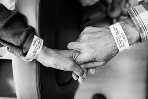 Like wedding rings, Laurel and Howie Borowick wear similar medical bracelets, which the nurses scan throughout their chemotherapy treatments together at the oncologists office. They do a dance, as both caretaker and patient and husband and wife, simultaneously trying to be there for the other but also trying to get through the day them selves. Greenwich, Connecticut. January, 2013 © Nancy Borowick