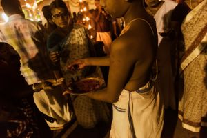A small brahmin boy blessing devotees at the temple. Kotakulangara, Kerala, India 2017