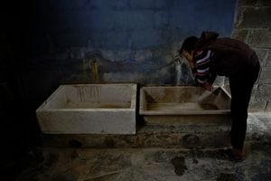 A boy washing his face at the camp's sanitational facilities. © Tom Verbruggen