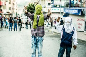 Far left-wing protesters of PKK youth organisation YDG-H armed with stones during clashes with riot police at anti-government demonstration in Istanbul's Gazi neighborhood, Turkey.
