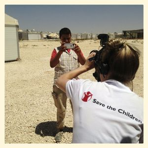 Omar* takes a picture while he is filmed by Save the Children staff