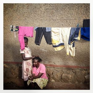 Two girls sit beneath clothes hanging on a washing line in Kibera. The Kibera slum is the largest slum in Nairobi with around half a million inhabitants.