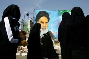 Iranian women walk past a portrait of Ayatollah Ruhollah Khomeini - the leader of the 1979 revolution and founder of the Islamic Republic of Iran. Tehran, IRAN - December 2008 © Copyright 1979-2009 Alfred Yaghobzadeh. All rights reserved.