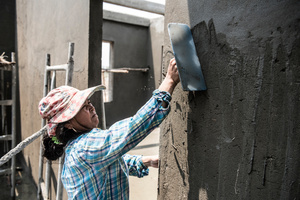 Meng Chan 38 from Prey Veng Province skims the walls of a newly constructed house with concrete. Chan has been working in construction for 2 years now. Chan believes she works as hard as the men and also has the same skills as the male workers.