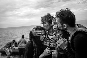 A Syrian family weeps tears of joy after reaching, on a rubber boat from Turkey, the village of Skala Sykaminiaslocated on the northeastern Greek island of Lesbos, on October 10, 2015.