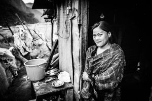 A resident of the village of Baluwa, Gorkha District, in front of a temporary shelter in which she is living with her parents, two sisters, and grandfather.