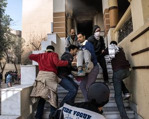 A man injured by burns is brought safely out of a school attacked by protesters on Joussef El-Gendy not far from Mahammed Mahmoud street. © Domenico D'Alessandro