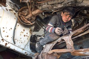 An eight-year-old boy collects precious copperwire for sale at the scrapyard to support his family.