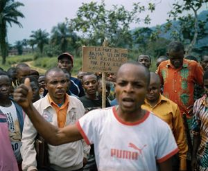 "Angry villagers at Damas' funeral hold up a sign reading, ""The death of Damas is a project realized by PIN in Lulingu on January 17, 2014."" The murder of Damas implicated an employee of the international nonprofit People in Need, who was accused of enlisting the murderer to commit the act, and RM soldiers who were said to have the murderer  to escape from the town prison. © Diana Zeyneb Alhindawi"