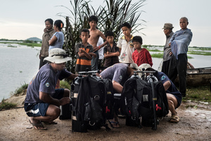 Members of the UXO salvage dive team prepare dive equipment on the banks of the Tonle Sap river overlooked by local villagers.