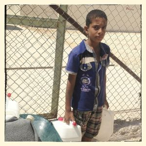 A young boy waits to refill his family water containers in Za'atari refugee camp