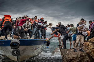 Refugees and migrants reach the coast of the Greek island of Lesbos after crossing the Aegean sea from Turkey on October 11, 2015.