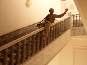 Tikrit April 14, 2003. In Saddam Hussein's hometown, a US Marine slides down a marble handrail in one of the dictator's extravagant palaces. The residence contained priceless carpets and at least one golden toilet. Tikrit was the last major city to fall to Allied forces during the invasion. Although fighting continued throughout Iraq, Marines celebrated victory. © Ashley Gilbertson/VII