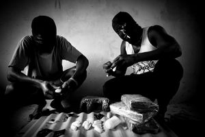 Two Nigerians affiliated with a Guinean drug trafficking ring prepare capsules containing cocaine that will be swallowed and then smuggled into Europe.  © Marco Vernaschi, 2009