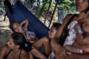 A group of girls relaxes on a hammock at 'Ilha da Resaca'. The whole colony will most probably cease to exist as soon as soil exploitation made by foreign enterprises will start in the area.  © Dario Bosio/Parallelozero