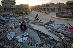 A Kurdish boy going through some books left in a destroyed building in Azadi square in Kobane on 20 April, 2015