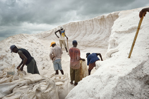 Workers package salt mined from a salt hill. Salt mining at Lac Rose, also known as Lake Retba.