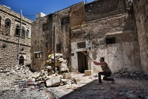An FSA fighter prepares to fire a rock with a slingshot toward Syrian army positions in the Old City of Aleppo on April 25, 2013. The historic Old City, a UNESCO World Heritage Site, has sustained a significant amount of damage during fighting between opposition groups and the Syrian government during the ongoing conflict. © Nish Nalbandian