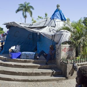 After the January 12, 2010, earthquake, the capital's public squares were taken over by displaced people living in tents. Here, an equestrian statue of Jean-Pierre Boyer, president from 1818 to 1843, is used to support a tent made of tarps from international aid organizations. Place Boyer, Pétion-Ville. Haiti. 2011. © Paolo Woods/INSTITUTE