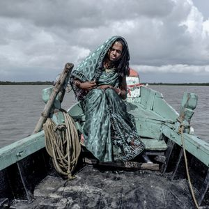 """A transgender person travels back home by boat after a money-collecting effort in the Sundarbans. From the series, """"Shunyo Raja,"""" 2017 © Courtesy East Wing."""