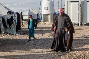 17/01/2015 -- Kirkuk, Iraq -- Suleiman Muhammad and the son of his daughter walk in front of their tent at Laylan IDP camp, south of Kirkuk.